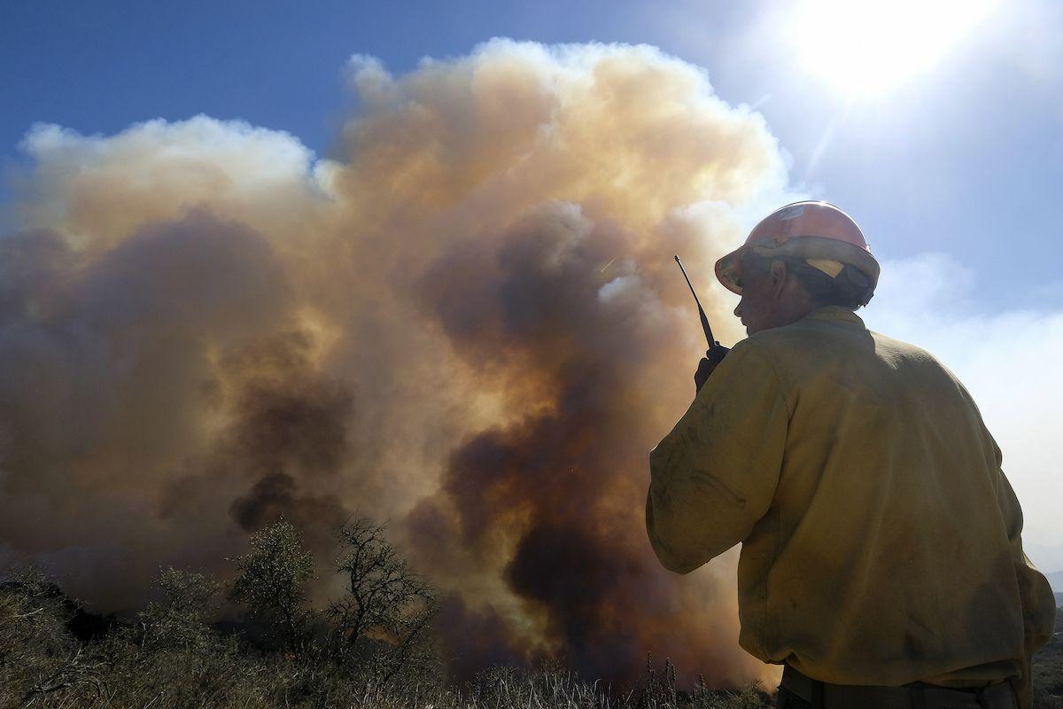 En esta foto del 13 de octubre del 2021, un bombero mira el humo de un incendio forestal en Goleta, California. El empeoramiento de los cambios climáticos requiere que Estados Unidos haga mucho más para monitorear, aliviar y manejar los flujos de refugiados que escapan de desastres naturales, dijo el jueves el gobierno de Joe Biden, en lo que calificó del primer examen federal profundo del problema.