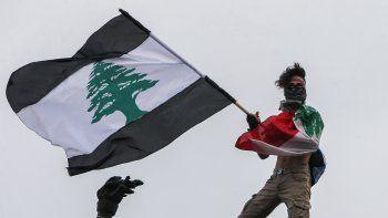 Un manifestante con una bandera libanesa con rayas negras se encuentra sobre la estatua de los mártires en la Plaza de los Mártires en el centro de la capital del Líbano, Beirut, durante una manifestación contra el gobierno el 1 de septiembre de 2020.