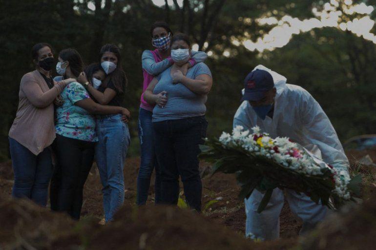 Familiares de una víctima de la enfermedad del nuevo coronavirus COVID-19 lloran mientras su ser querido es enterrado en el cementerio de Vila Formosa en Sao Paulo