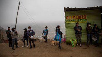 Unas personas se forman para recibir alimentos en comedores comunitarios en el vecindario Nueva Esperanza, en Lima, Perú, el miércoles 17 de junio de 2020.