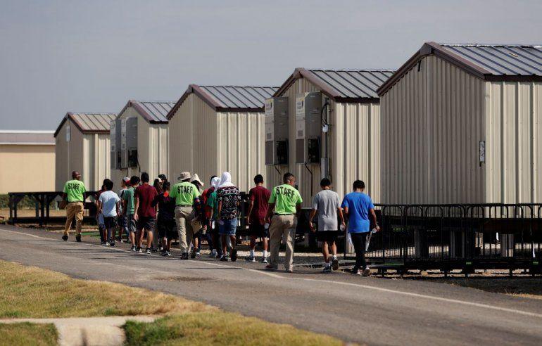 Miembros del personal escoltan a unos menores a una clase en un centro de detención para niños migrantes del gobierno de Estados Unidos en Carrizo Springs