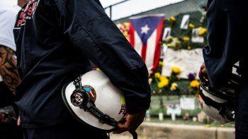 Los rescatistas visitan y presentan sus respetos a los familiares de las víctimas en el Surfside Wall of Hope & Memorial cerca del sitio del edificio derrumbado en Surfside, Florida, al norte de Miami Beach.