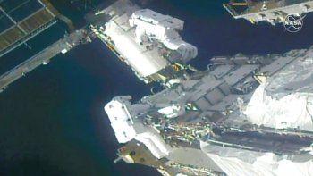 Los astronautas de la NASA Kate Rubins y Victor Glover trabajan afuera de la Estación Espacial Internacional (EEI) en el montaje de los soportes para la instalación de nuevos páneles solares.