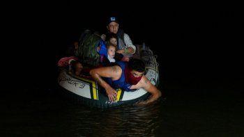 En esta foto del 30 de marzo del 2021, un contrabandista lleva a migrantes, mayormente centroamericanos, en una balsa inflable hacia Estados Unidos, en Roma, Texas.
