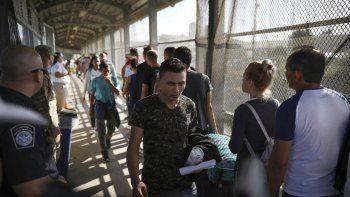 En esta fotografía de archivo del 2 de febrero de 2019, los migrantes regresan a México mientras otros hacen fila en su camino para solicitar asilo en los Estados Unidos, al pie del puente la Puerta México en Matamoros, México, que cruza hacia Brownsville, Texas.