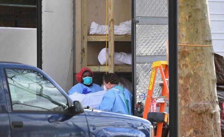 El personal médico lleva a un paciente fallecido a un camión frigorífico que funciona como morgue provisional en el Centro Médico Judío Kingsbrook