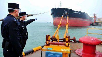 Funcionarios chinos supervisan la llegada de un buque cisterna con 230.000 toneladas de petróleo procedente de los Emiratos Árabes Unidos en el puerto Qingdao el 26 de marzo del 2020. China está aprovechando los precios bajos del petróleo para aumentar sus reservas.