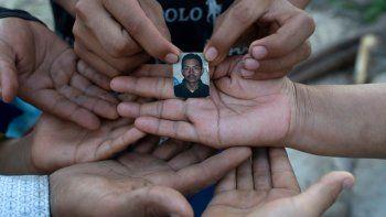 La salvadoreña Rebeca Valle de Barrera (R) y sus cinco hijos muestran una foto de su difunto esposo Joaquín Barrera quien, junto con sus padres y otros dos hermanos, murió recientemente de COVID-19, en su casa en Santiago Nonualco, departamento de La Paz. , El Salvador, el 23 de julio de 2020.