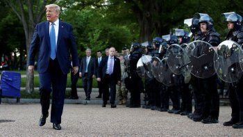 El presidente Donald Trump camina el lunes 1 de junio de 2020 junto a agentes policiales en el parque Lafayette frente a la Casa Blanca, en Washington.