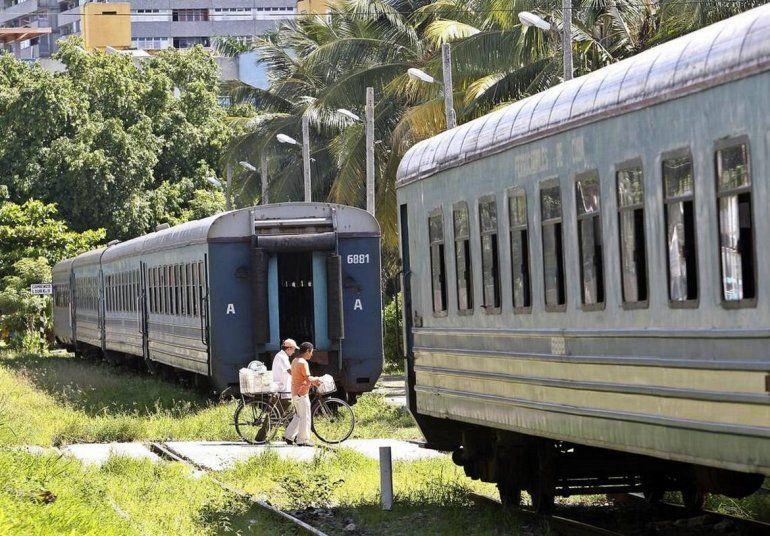 Fotografía de archivo fechada en agosto de 2018 de dos personas que caminan entre dos vagones de un tren de pasajeros en las inmediaciones de una estación de trenes en La Habana