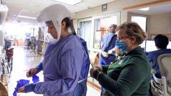 En esta fotografía del 5 de noviembre de 2020, Deb Dalsing, enfermera de la unidad de COVID-19 del hospital UW Health, ayuda a la enfermera Ainsley Billesbach con su equipo de protección, en Madison, Wisconsin.
