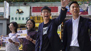 El candidato ganador de las elecciones locales Kelvin Lam, a la derecha, junto al activista prodemocracia Joshua Wong, segundo por la derecha, saludan a la gente y dan gracias por el apoyo en la estación South Horizons de Hong Kong, el lunes de noviembre de 2019.