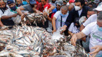 Residentes de un barrio popular de Caracas toman pescado durante un mitin de campaña organizado por Javier Bertucci y Juan Eleazar, ambos candidatos a las elecciones parlamentarias, convocadas por el régimen.
