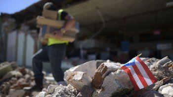 Una bandera de Puerto Rico se ve colocada entre los escombros, mientras los propietarios y familiares retiran suministros de la ferretería Ely Mer Mar, parcialmente derruida tras un terremoto en Guanica, Puerto Rico, el martes 7 de enero de 2020.