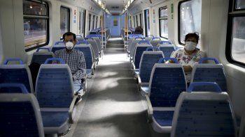 En esta foto de archivo del 20 de marzo de 2020, personas con máscaras como medida de precaución en medio de la propagación del nuevo coronavirus viajan en un tren vacío en Buenos Aires, Argentina.