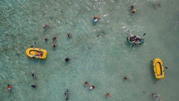 La gente nada y juega con botes en el Cayo Playuela del Parque Nacional Morrocoy, estado Falcón, Venezuela, el domingo 13 de junio de 2021. En medio de la pandemia, muchos de los sitios de turismo apenas logran sobrevivir.