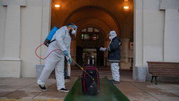 Un empleado en traje de protección desinfecta el equipaje de un pasajero frente a la terminal de la empresa argentina de servicios de ferry Buquebus en el puerto de Montevideo, el 10 de julio de 2020, en medio de la nueva pandemia de coronavirus.