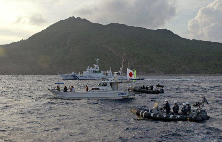 Un barco de la Guardia Costera de Japón navega cerca de otros barcos advirtiendo que se alejen de un grupo de islas en disputa por Japón y China