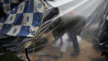 Un inmigrante venezolano desempleado y sin hogar viste a su hijo dentro de una carpa cerca de la terminal principal de autobuses en Bogotá, Colombia, el miércoles 3 de junio de 2020. Frente a las restricciones de viaje y sin trabajo debido al cierre económico para frenar al COVID-19, los migrantes venezolanos acampan a la espera de ayuda para volver a su país.