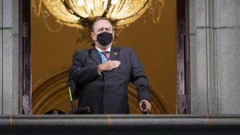 El presidente de Guatemala, Alejandro Giammattei, con una mascarilla protectorapor el coronavirus COVID-19, canta el himno nacional durante la celebración del día de la independencia en la Ciudad de Guatemala.