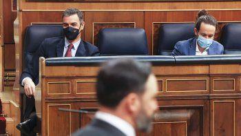 El líder de VOX, Santiago Abascal, pasa frente al presidente del Gobierno de España, Pedro Sánchez (i) y el vicepresidente segundo, Pablo Iglesias (d), en el pleno del Congreso.
