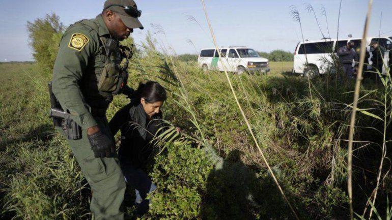 Un agente de Aduanas y Protección Fronteriza detiene a una persona inmigrante que cruzó ilegalmente hacia Estados Unidos por el Rio Grande (río Bravo para México) cerca de Granjeno
