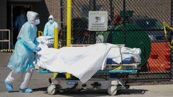 Personal médico traslada los cuerpos a un camión de refrigeración que sirve como depósito temporal de cadáveres en el Hospital Wyckoff en Brooklyn, Nueva York, el 6 de abril de 2020.