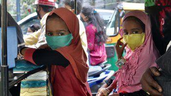 Los niños que viajan con sus padres en un auto rickshaw usan una máscara facial como medida preventiva contra el coronavirus COVID-19, en Bangalore, el 27 de julio de 2020.