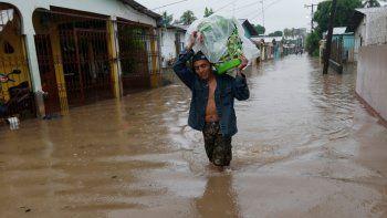 Un hombre camina por una calle anegada, con el agua a la altura de las rodillas, llevando sus pertenencias a cuestas, en San Manuel, Honduras, el 4 de noviembre de 2020