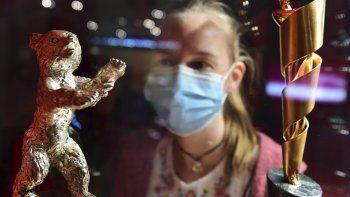 En esta foto del 14 de mayo de 2020, una chica con mascarilla mira un Oso de Oro de la Berlinale y un Lola durante la exposición Traumfabrik, 100 años de cine en Babelsberg en Berlín. El Festival Internacional de Cine de Berlín anunció el jueves las 15 películas que conformarán la competencia este año.