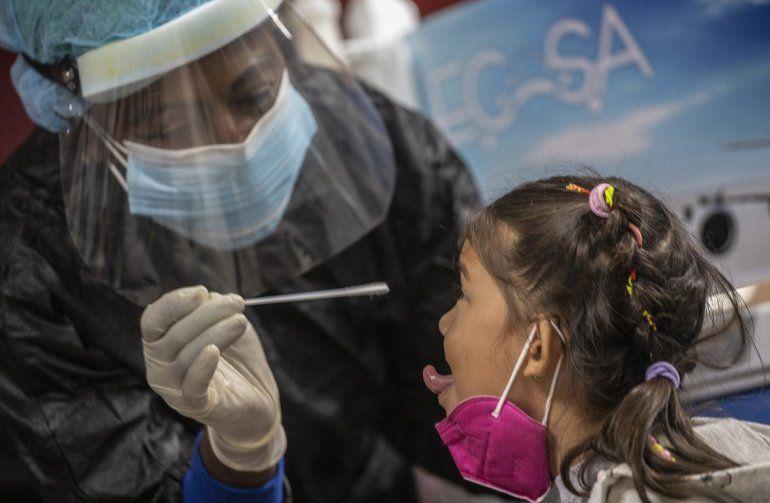 Una empleada de salud toma una muestra para una prueba de COVID-19 a una niña que acaba de llegar desde Cancún