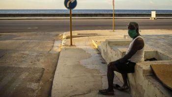 Un hombre que usa una máscara como precaución contra la propagación del nuevo coronavirus descansa en el malecón del malecón en La Habana, Cuba, el lunes 31 de agosto de 2020.