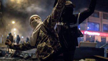 Un hombre con máscara y capucha arroja piedras a la policía el jueves 10 de septiembre de 2020 durante protestas por la muerte de un hombre a manos de la policía, en Bogotá, Colombia.