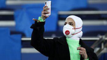 Una aficionada toma una fotografía con su teléfono celular antes del partido entre el Real Madrid y el Manchester City en el Estadio Santiago Bernabeu de Madrid.