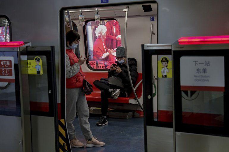 Viajeros con mascarillas leen en sus teléfonos celulares en el metro de Beijing. El organismo supervisor del internet en China obligará a los blogueros e influencers adquieran una licencia para poder publicar opiniones sobre ciertos temas.