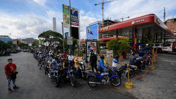 Los transeúntes esperan en la cola para repostar los tanques de su motocicleta con gasolina en una estación de servicio, en Caracas, el 7 de abril de 2020 en medio del nuevo brote de coronavirus (COVID-19). La economía de Venezuela atraviesa una crisis sin precedentes.
