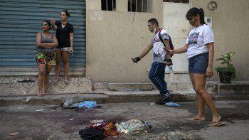 Residentes de acarezinho toman fotografías de pertenencias cubiertas de sangre de personas asesinadas durante un operativo policial contra presuntos narcotraficantes en la favela Jacarezinho en Río de Janeiro, Brasil, el 6 de mayo de 2021.