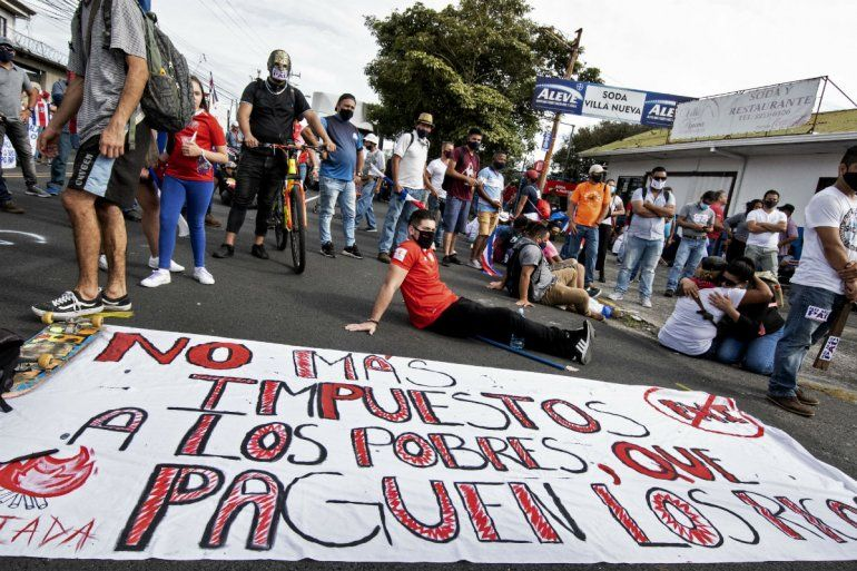 La gente se manifiesta junto a un cartel que dice No más impuestos a los pobres