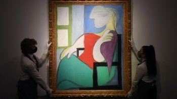 En esta foto de archivo tomada el 22 de abril de 2021, los trabajadores de la galería muestran una obra de arte titulada Femme assise près dune fenêtre (Marie-Thérèse) del pintor español Pablo Picasso durante un photocall en la casa de subastas Christie en el centro de Londres.
