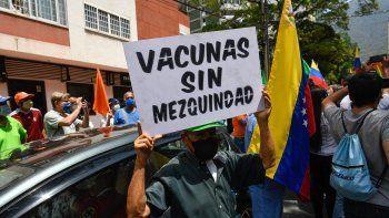 """Un activista sostiene un cartel que dice """"Vacunas sin mezquindad"""" durante una protesta de venezolanos para exigir que todos los trabajadores de la salud sean vacunados contra el COVID-19, en la plaza Los Palos Grandes, en Caracas el 17 de abril de 2021."""