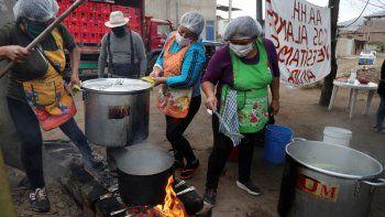 Mujeres preparan comida para un grupo de familias que enfrentan dificultades por la pandemia del nuevo coronavirus en Villa María del Triunfo en Lima, Perú.