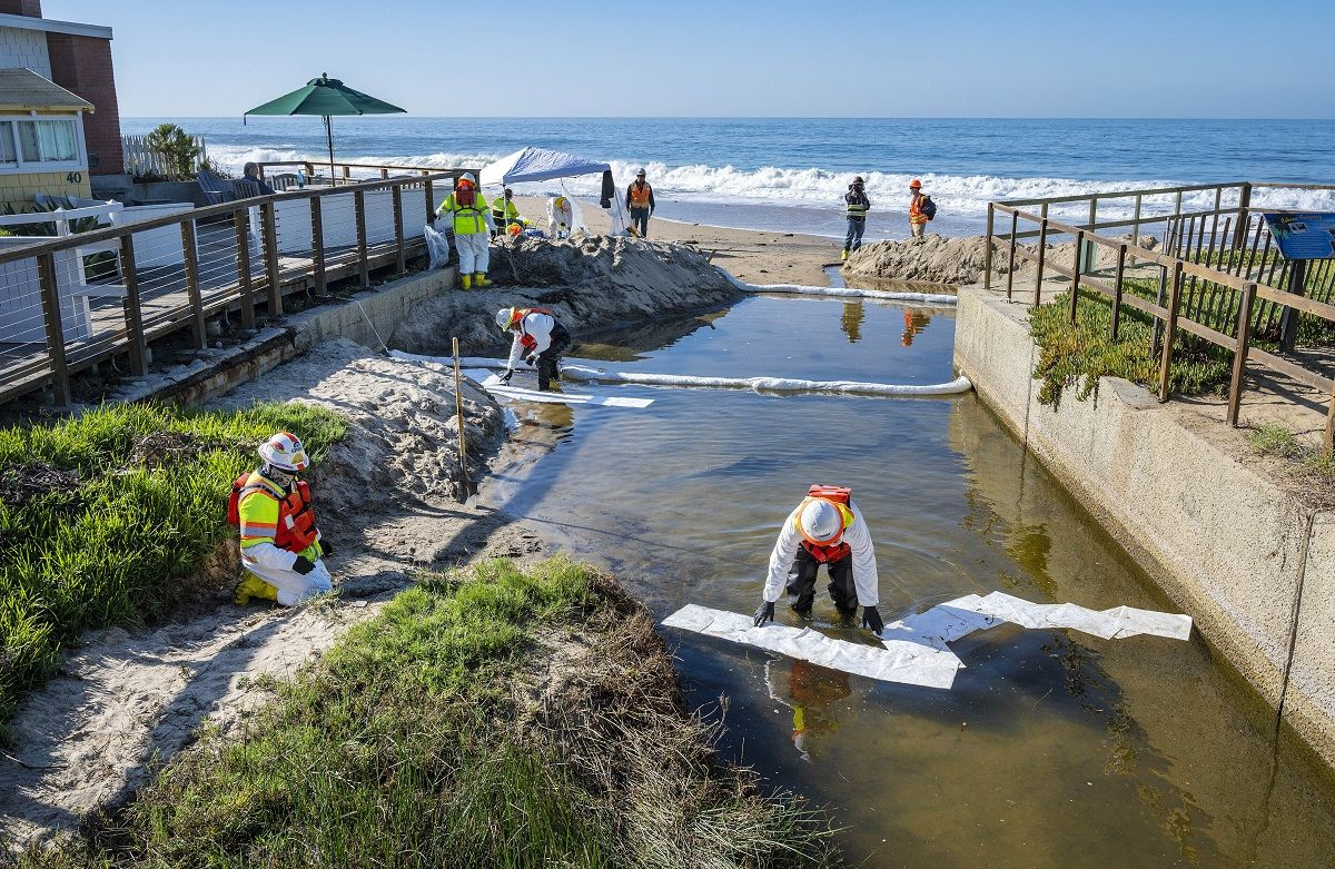 Equipos de limpieza utilizan material absorbente para retirar petróleo que pudiera haber ingresado a un pequeño riachuelo que desemboca en el océano, luego de una fuga en un oleoducto, el jueves 14 de octubre de 2021, en Laguna Beach, California.
