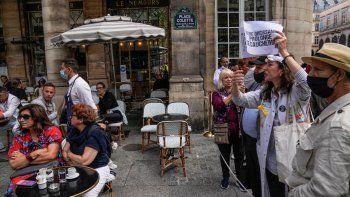 Manifestantes protestan contra el pase especial por COVID-19 junto a un café al aire libre cerca del Tribunal Constitucional de París el jueves 5 de agosto del 2021