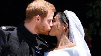 En esta foto de archivo tomada el 19 de mayo de 2018, el príncipe Harry de Gran Bretaña, duque de Sussex besa a su esposa Meghan, duquesa de Sussex, al salir de la puerta oeste de la capilla de San Jorge, en el castillo de Windsor, en Windsor, el 19 de mayo de 2018 después de su ceremonia de la boda.