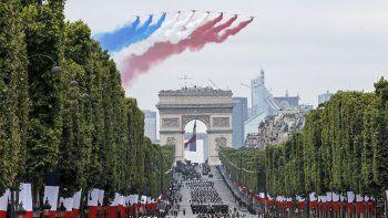 Aviones franceses dejan líneas de humo con los colores de la bandera francesa sobre la avenida de los Campos Elíseos durante el desfile por el Día de la Bastilla en París, el domingo 14 de julio de 2019.