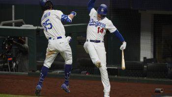El jugador de los Dodgers de Los Ángeles Cody Bellinger celebra su jonrón con Kiké Hernández, en el séptimo juego contra los Bravos de Atlanta por el campeonato de la Liga Nacional, el domingo 18 de octubre de 2020 en Arlington, Texas.