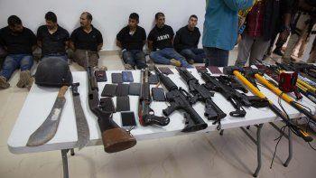 Varios detenidos por el asesinato del presidente haitiano Jovenel Moise son presentados a los reporteros junto con las armas y equipo que supuestamente utilizaron en el ataque, durante una conferencia de prensa el jueves 8 de julio de 2021 en la Dirección General de Policía, en Puerto Príncipe, Haití.