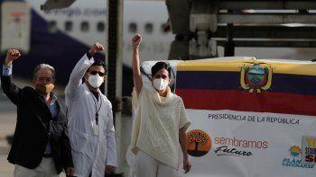 La vicepresidenta María Alejandra Muñoz, a la derecha, un médico, al centro, y el ministro de Salud, Juan Carlos Zevallos, levantan los puños mientras reciben las primeras 50.000 dosis de la vacuna Pfizer en el aeropuerto Mariscal Sucre de Quito, Ecuador, el miércoles 20 de enero de 2021.