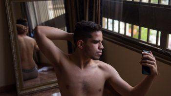Brandon Mena se toma fotos en un espejo con su celular, para hacer contenido para su perfil de OnlyFans, en Caracas, el 12 de noviembre de 2020. Los jóvenes venezolanos utilizan el servicio de suscripción de contenido en inglés OnlyFans para superar la crisis económica.