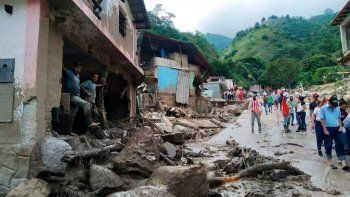 En esta foto proporcionada por la oficina de prensa del gobierno del estado de Mérida, personas caminan por una calle dañada por inundaciones y deslizamientos de tierra provocados por lluvias torrenciales en la zona del Valle del Mocoties del municipio de Tovar en el estado de Mérida, Venezuela.
